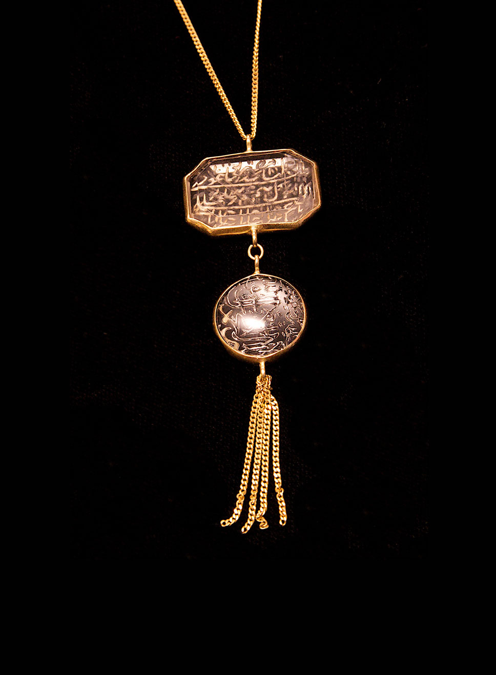 Antique Iranian prayer pendant. Crystal with a 22ct gold bezel and 18ct gold chain. Length of chain-93cm. Pendant height- 2cm. Width- 3cm.