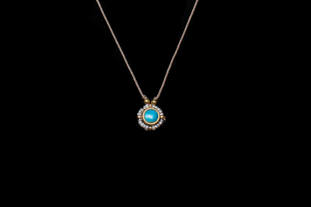 Turquoise daisy pendant surrounded by pearls & 22ct gold bezel on a silk thread. Necklace length 47cm. Pendant size- 2cm.
