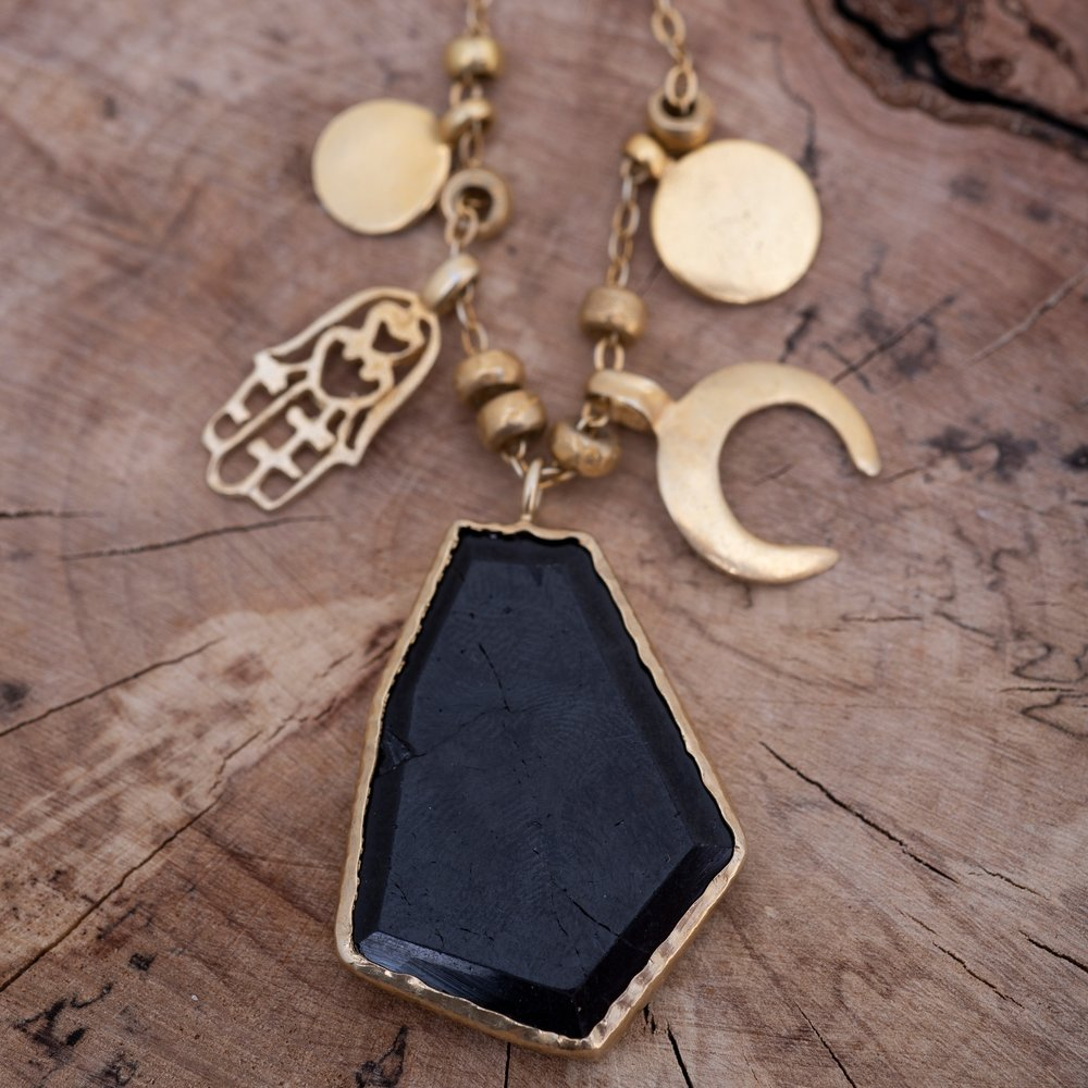 Bespoke Amulets Necklace. Black tourmaline, the protective hand of Fatima, a crescent moon for new beginnings, and sun pendants.
