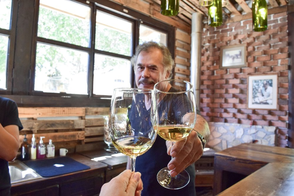 Toasting with a glass of Chardonnay with Owner and winemaker Reynaldo Rodriguez Sr. in their tasting room.
