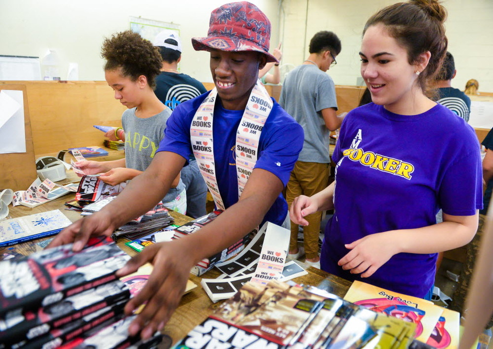 Booker High School students, from left, Charlotte Corporan, Nathan Miller and Dayan Ricardo sort through books at the Herald-Tribune Printing Press. The Community Foundation of Sarasota County will hand out the books to children and families throughout the county on July 14 as part of National Summer Learning Day. Photo by Dan Wagner.