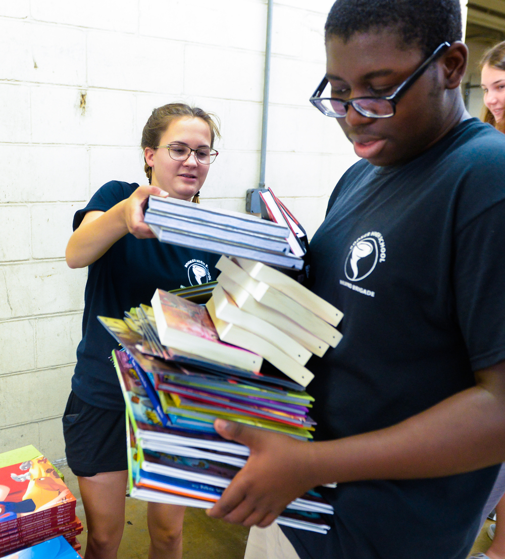 Booker High School students Leah Mehtala and Luigi Lockhart sort through books at the Herald-Tribune Printing Press on Wednesday. The Community Foundation of Sarasota County will hand out the books to children and families throughout the county on July 14 as part of National Summer Learning Day.