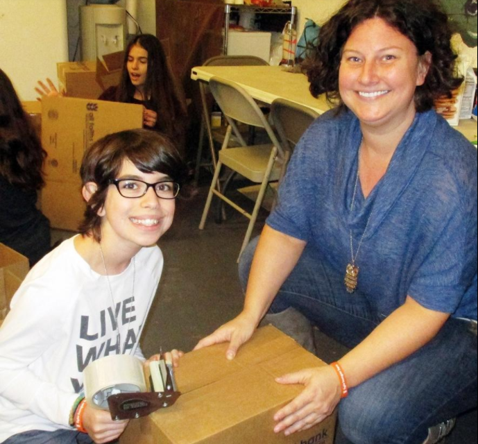 Lucy and Courtney Eiseman, volunteers with Temple Emanu-El, make boxes to help sort donated food at All Faiths Food Bank.