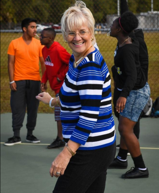Brenda Zofrea, an eighth-grade reading teacher at Booker Middle School, smiles while watching Josh McClelland and Ashley Drummonds lead students at the school in an exercise routine on Dec. 9.