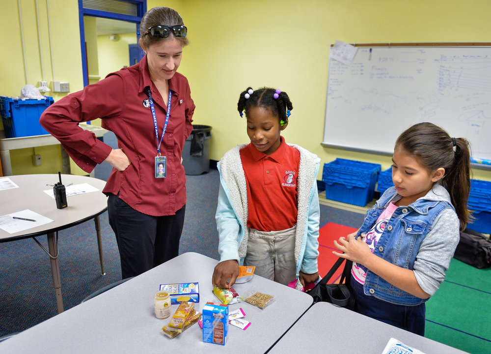 Gocio Elementary School third-graders Princess Houston, center, and Janellise Ridgway, right, tell school counselor Tracey Bailey what their favorite foods are in the Backpack Kids program. Herald-Tribune staff photo / Dan Wagner