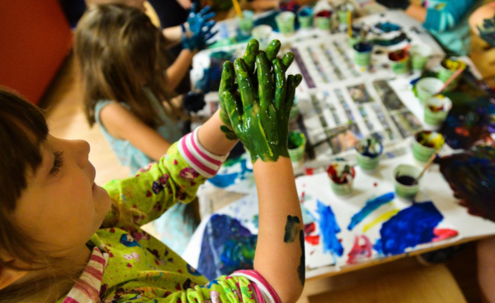 "Prekindergartener Mirabel Nieman uses finger paint to create a scene from ""Mouse Paint."" [Herald-Tribune staff photo/Dan Wagner]"