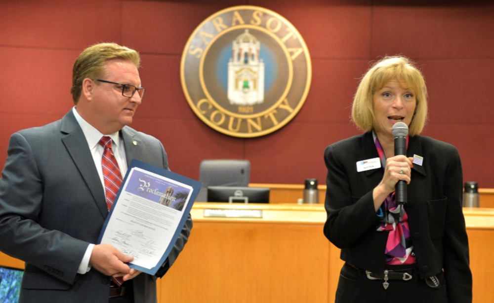Beth Duda, Director of the Suncoast Campaign for Grade-Level Reading, accepts a proclamation presented by Sarasota County Commissioner Michael Moran declaring April Reach out and Read Month at the county commission meeting Tuesday, Mar. 21, 2017. [Herald-Tribune staff photo / Mike Lang]