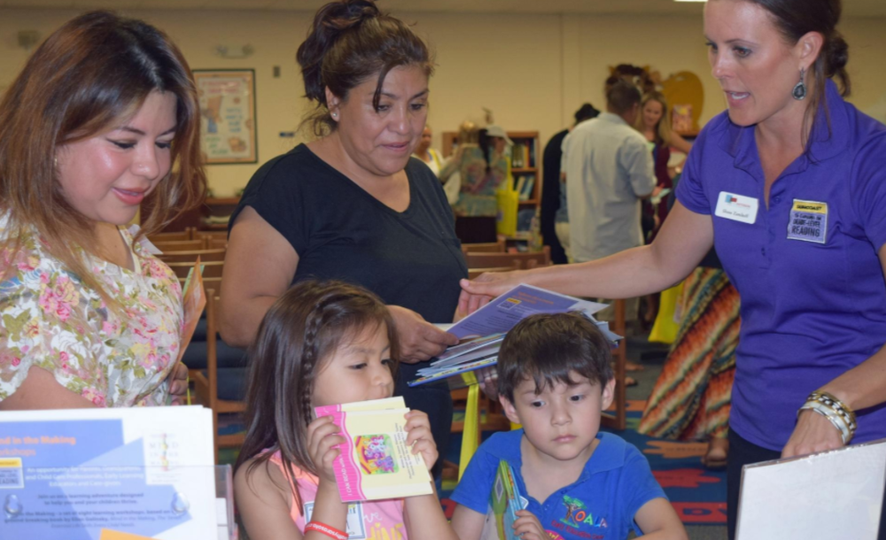 (From left to right) Laura Lopez and Martha Villavicencio, parents of incoming kindergartners, talk about free literacy app Vroom with Shana Zamikoff, member of the support outreach team for the Suncoast Campaign for Grade-Level Reading at Alta Vista's kindergarten roundup on Tuesday. [Herald-Tribune photo/Yadira Lopez]
