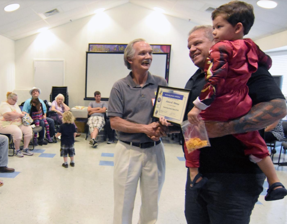 Robert Phinney is given a certificate from Jack Baker when he graduates from the Nuturing Dads program for new dads, expectant dads, married or single dads held at Children First. The class is helping area fathers be the best caretakers they can be and empower them to be pillars in their child's lifelong success. Three year old Henry Phinney is also in photo. [Herald-Tribune photo/Carla Varisco]