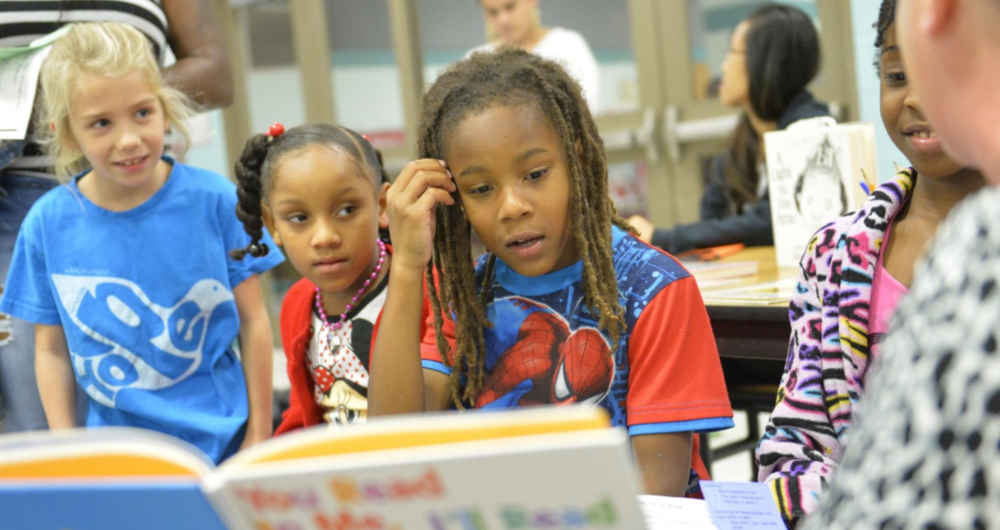 Angel Kingsburry, 8, Jasiyah Harrell, 6, and Jason Harrell, 3rd grade, read poetry with teacher, Cyndi Brigance, right, at Oneco Elementary school in Bradenton. The Campaign for Grade-Level Reading is a national effort aimed at third grade students. [Photo courtesy of Herald-Tribune/Thomas Bender/2013]