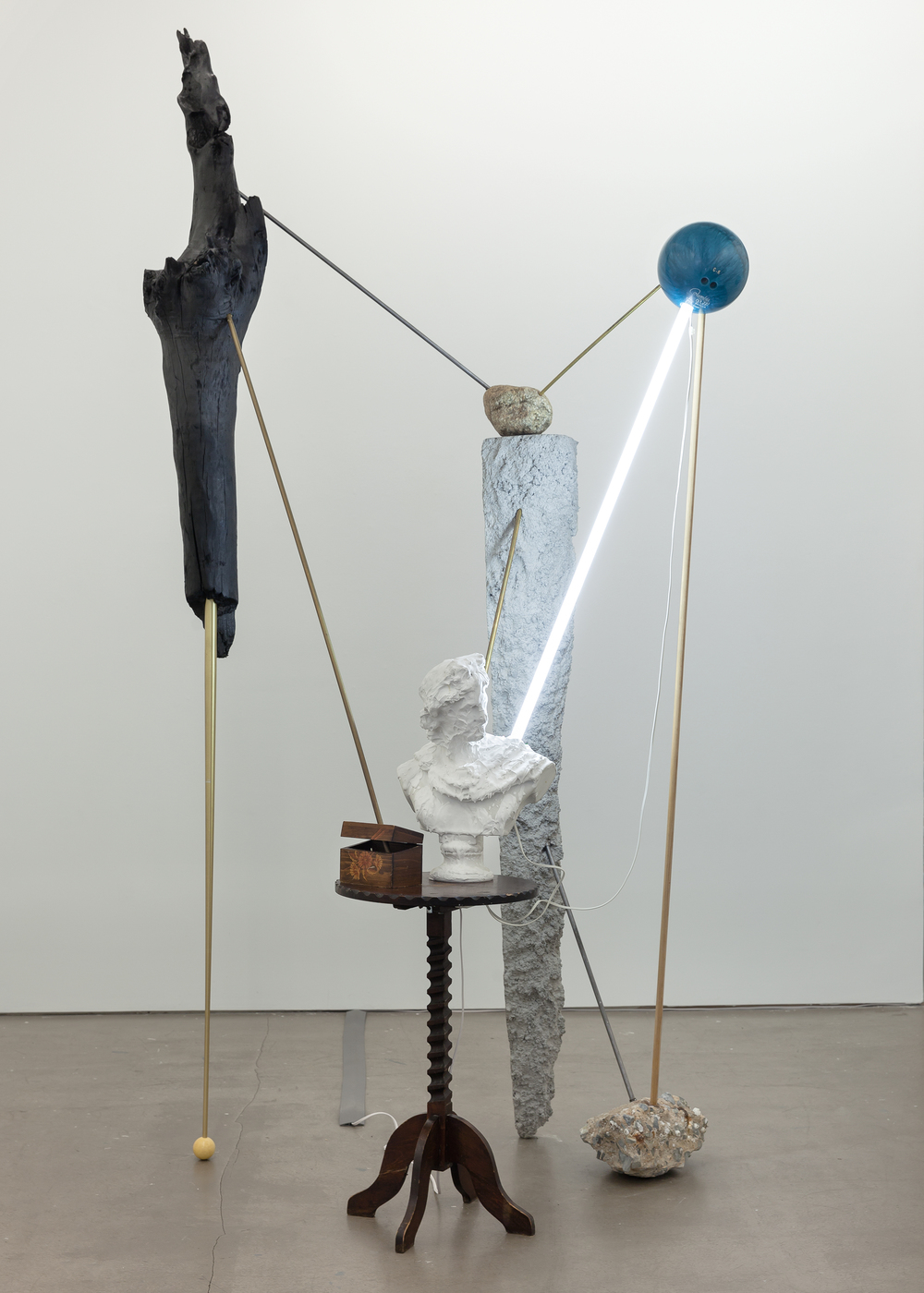 Alejandro Almanza © 2014 ,  Sticks and stones.  Concrete, brass, aluminum, bust, table, found rocks, cue ball, drift wood, bowling ball, fluorescent light bulb. Courtesy of the artist.