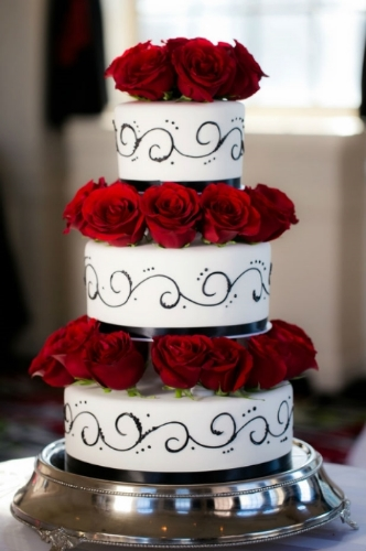 A simple black and white wedding cake is made stunning with red roses.
