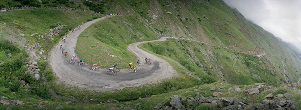 Celebrating the 100th Tour de France, the iconic Alpe d'Huez climb was ascended twice in a row for the first time in 2013.  Here cyclists navigate downhill through infamous hairpin turns, which were closed to the public before the second climb. Huez, France 2013.