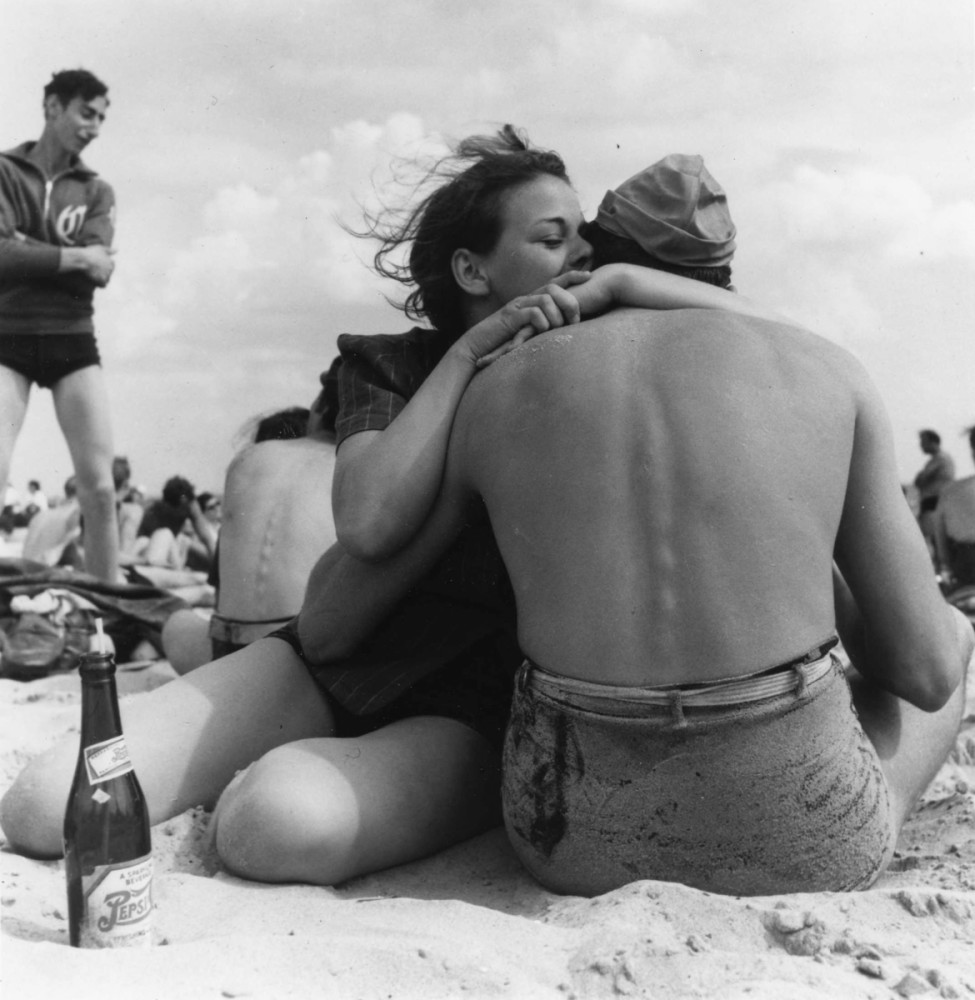 1938: A couple sitting embraces on a crowded beach. Coney Island, Brooklyn. New York, New York, 1938. 01/01/1938 Photo by Morris Engel/Getty Images