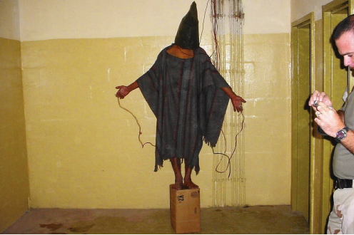 An Iraqi detainee at Abu Ghraib prison stands on a box with wires attached as he is photographed by U.S. military personal. November 4, 2003.