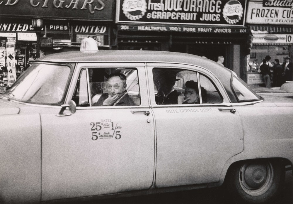Taxicab driver at the wheel with two passengers, N.Y.C. 1956 © The Estate of Diane Arbus, LLC. All Rights Reserved