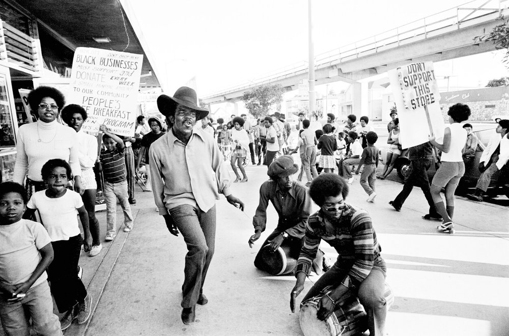 Image Above: The Lumpen, the Panthers' singing group, performs at the boycott of Bill's Liquors, Oakland, 1971. Clark Bailey, known as Santa Rita, is dancing. Michael Torrence (front) and James Mott (back) are drumming. All images: Stephen Shames, Courtesy of Steven Kasher Gallery