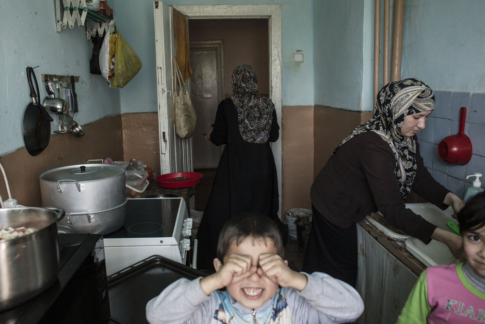 Mariam Muslimova (R) and Khadija Adamova are making dinner while their kids are playing in the kitchen. Both Mariam's and Khadija's families left Crimea after the Russian annexation in February 2014 and moved to the village Borynia, Lviv area, Western Ukraine where they live in a dormitory of a local college © Anastasia Vlasov.