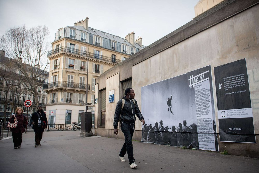 "©Benjamin Girette. For COP21, we teamed up with the Magnum Foundation, Yale School of Forestry and Environ-mental Studies, NYU-ITP Students & Twillio to #reframeclimate by pasting current photojournalism in the streets of Paris. Pictured is Katie Orlinsky's photograph that was pasted in Paris. The caption reads: The traditional blanket toss at the annual whaling feast in Point Hope, Alaska on June 16, 2015. For the Inupiat villagers of Point Hope, nothing is more important than the bowhead whale. The calendar year revolves around hunting, fishing and gathering, a lifestyle Alaskans call ""subsistence,"" which is as much cultural tradition as economic necessity. The entire village looks for-ward to spring whaling, and celebrates a successful hunt with an annual feast.  In recent years, however, the much-anticipated whale hunt has run up against a warming Arctic. Ice is getting thinner, windows of opportunity for hunting are shrinking and animal behavior is changing. Alaska had its hottest year on record in 2014, and for Inupiat villagers in Point Hope who have hunted and foraged their meals for generations, climate change now threatens their way of life."