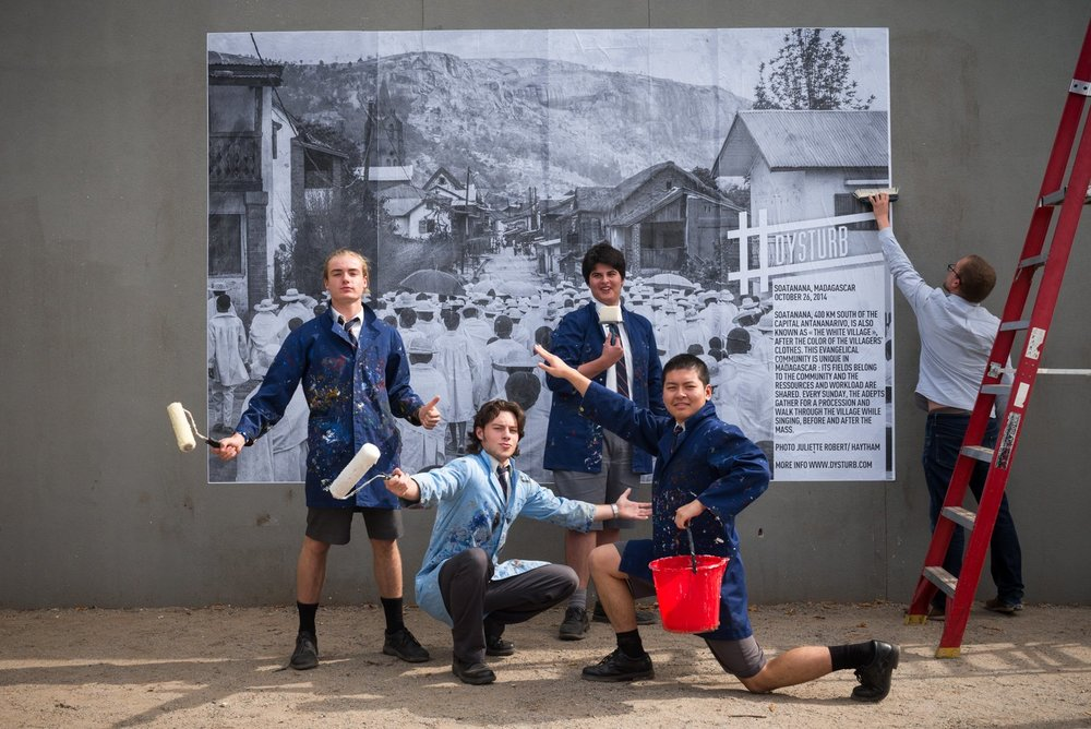 "©Madélena Rehorek. Earlier this year, McKinnon Secondary College students finish pasting Juliette Robert's (Hay-tham Pictures) photograph of Madagascar's evangelical community. The caption reads: Soatanana, Madagascar. October 26, 2014. Soatanana, 400 km south of the capital Antananarivo, is also known as ""The white village,"" after the color of the villagers' clothes. This evangelical community is unique in Madagascar: Its fields belong to the community and the resources and workload are shared. Every Sunday, the adepts gather for a procession and walk through the village while singing, before and after the mass."