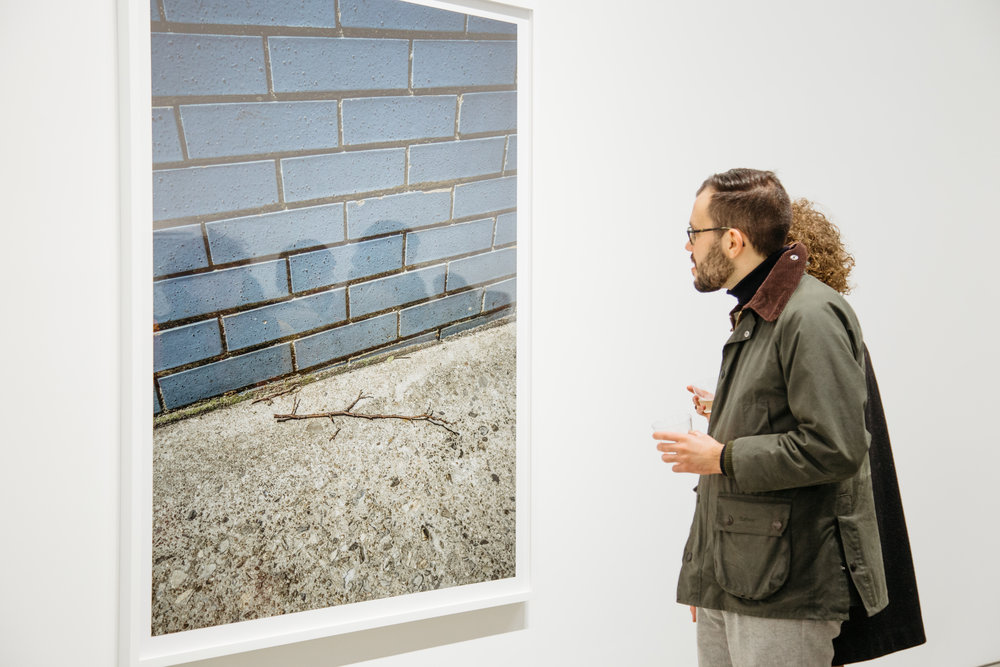 Gallery attendees are shown alongside Stephen Shore's  New York, New York, May 19,2017  © Nicole Angeles