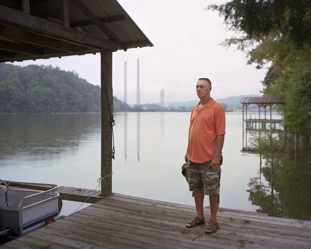"""Glenn, Kingston Coal Ash Spill, Clinch River, Tennessee"" 2009  © Jeff Rich    When I photographed Glen, nine months after the Kingston Harriman Coal Ash Spill, he was in negotiations with the TVA for the purchase of his home. The TVA was buying up much of the property surrounding the spill as a way to pay reparations. They were buying Glen's property below market value. In 2015 the TVA held an auction and netted $9.1 million from reselling these homes to new owners."