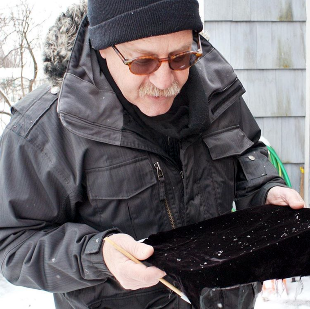 Michael Peres catching snowflakes on a black velvet catch tray.© Michael Peres