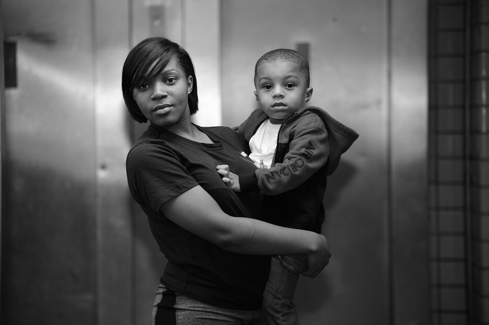 Claremont resident, Shaquesha Hairston and son, waiting in the lobby area of 1385 Washington Avenue. Morris I Projects, Bronx NY. July 26, 2017.  © Ed Alvarez/Bronx Photo League