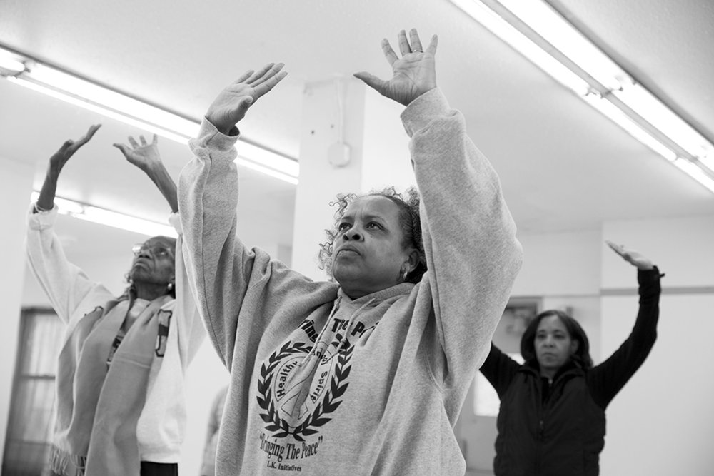 Residents of 540 East 169th Street do Tai Chi in their building's Community Room on February 13, 2018.  © Belinda Gallegos/Bronx Photo League