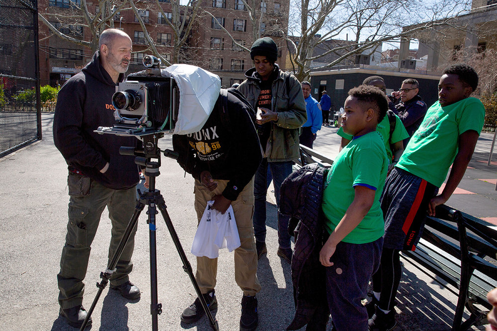 "Claremont's children take a look through a 5X7"" film camera in Drew Park on April 21, 2018.  © Belinda Gallegos/Bronx Photo League"