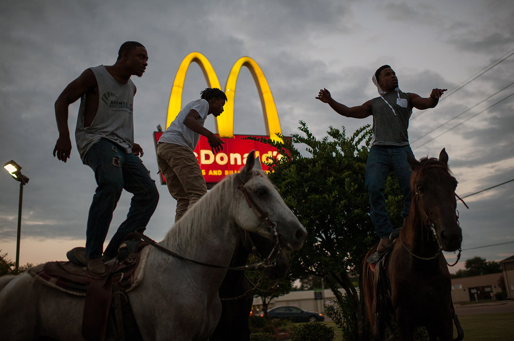 A group of young cowboys dance atop their horses outside McDonald's in Cleveland, Mississippi. Photo by Rory Doyle.
