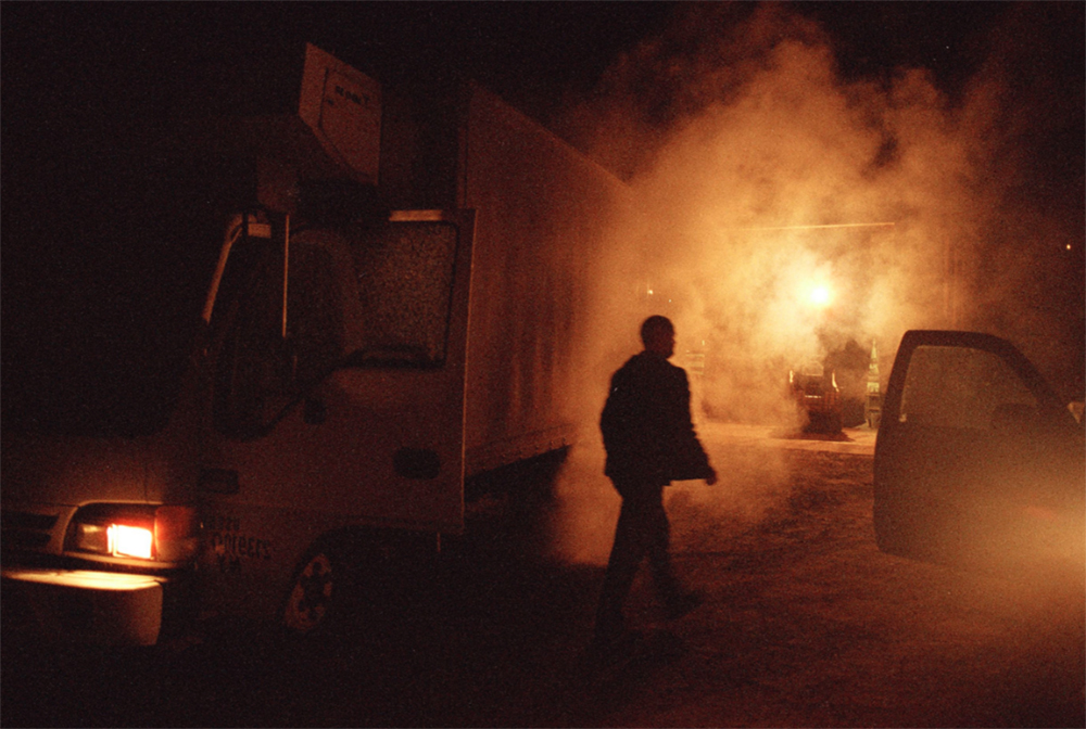 """""""Jason at 5am."""" In 2000 Holley White and Richard Giles moved from Texas to Hamden, NY to start Lucky Dog Farm. Here, Jason is loading the truck with organic produce to sell at the Union Square Greenmarket. © Tess Mayer"""