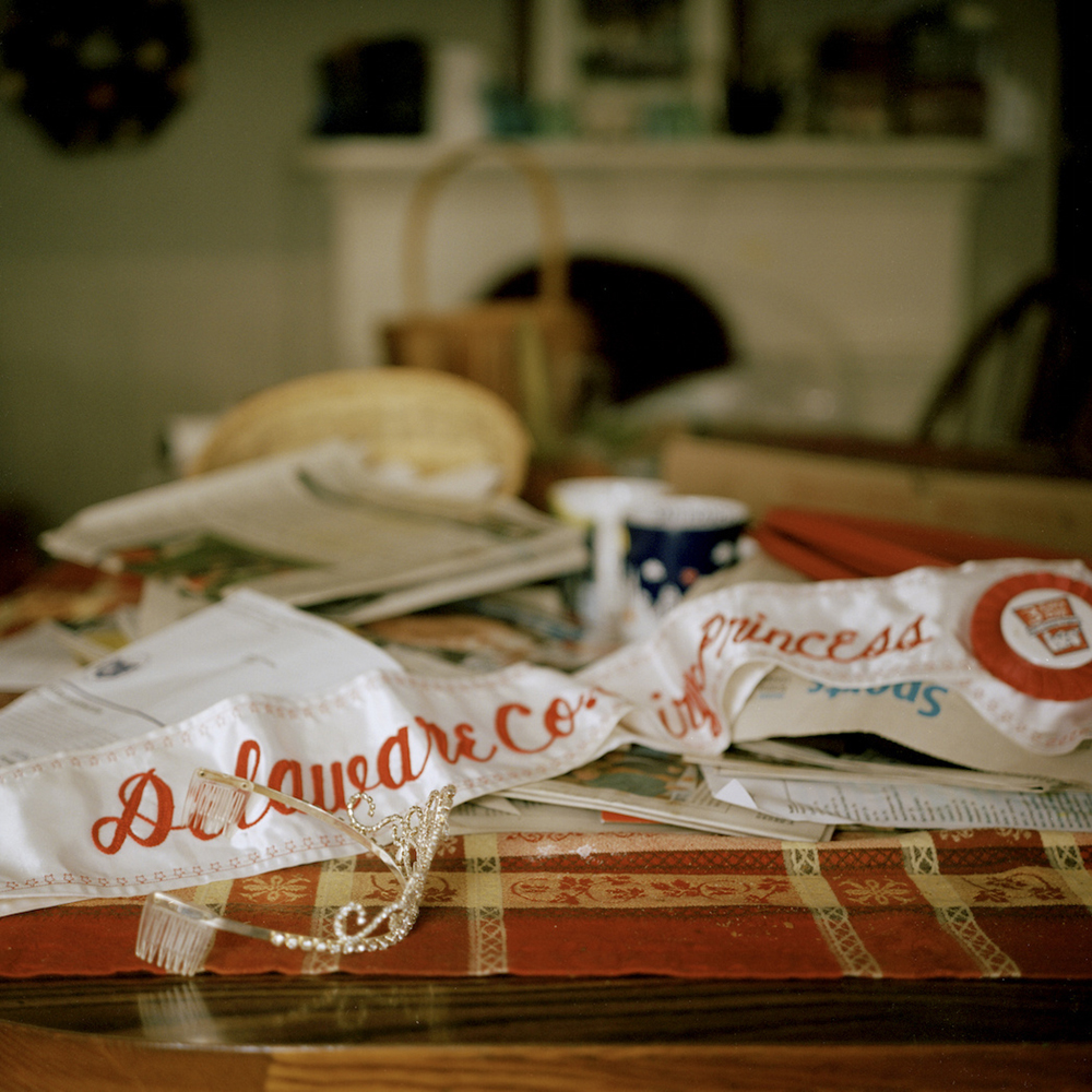 """""""Dairy Princess."""" Miquela Hanselman's Delaware County Dairy Princess sash on the dining table of her home. Miquela is the youngest of seven children, three of whom currently work on their parent's farm, Del-Rose Farm © Tess Mayer"""