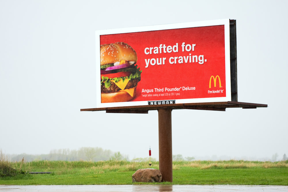 Fosston, Minnesota, USA - May 20, 2011: A Newman Signs billboard along US Highway 2 with advertising for McDonalds Restaurants, specifically for their Angus Third Pounder Deluxe.