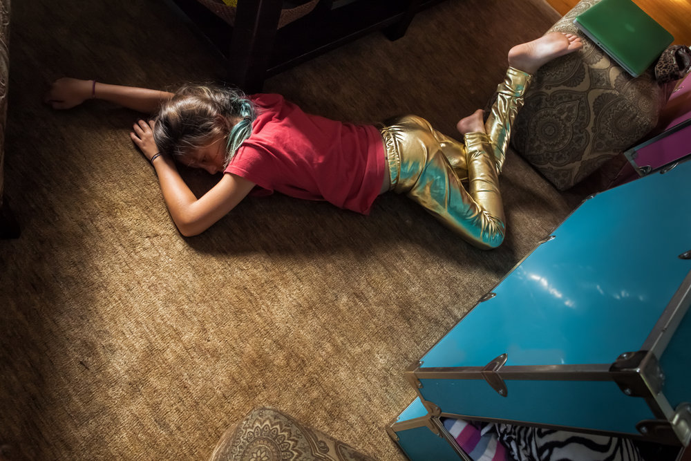 After Camp : My daughter had just returned from overnight camp. The first thing she did when she got home was open her trunk, put on- gold lamé pants, and lie down on the floor. Who does that? © Tira Khan