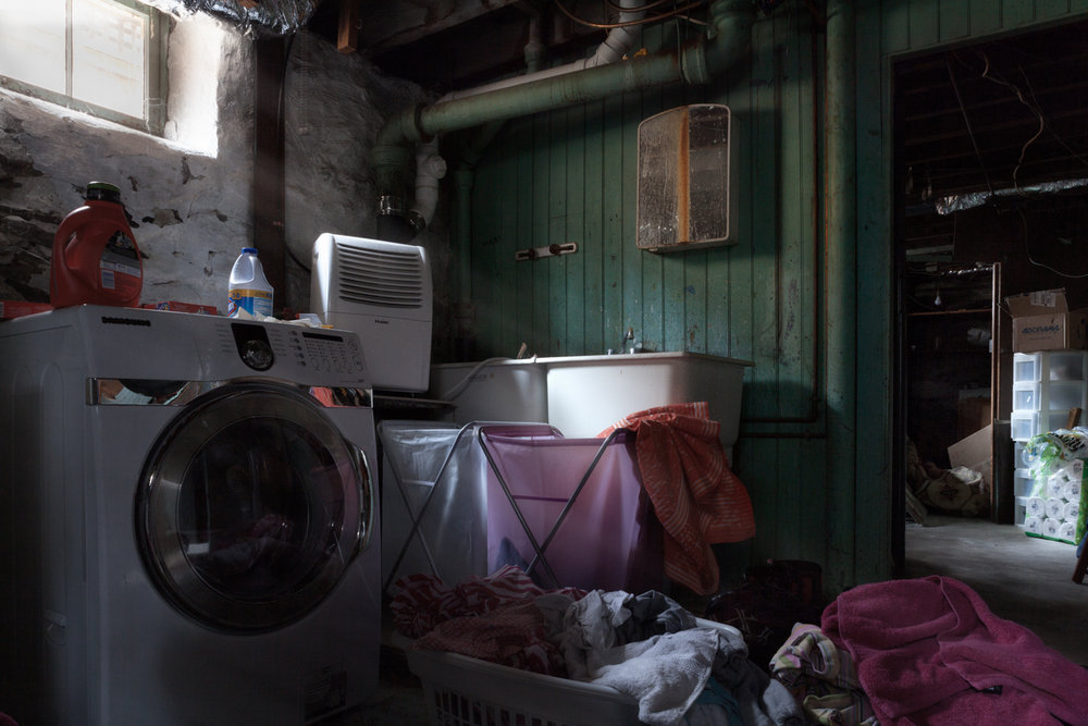 Where the Laundry Lives : Perhaps the scariest laundry room ever. For more than 10 years, I hated going down to the basement to do the laundry. The room was dark, and about 20 degrees colder than the rest of the house. My mother always bugged me to move the machines to another floor, but there was nowhere else to put them. Needless to say, the laundry often languished in the basement. © Tira Khan