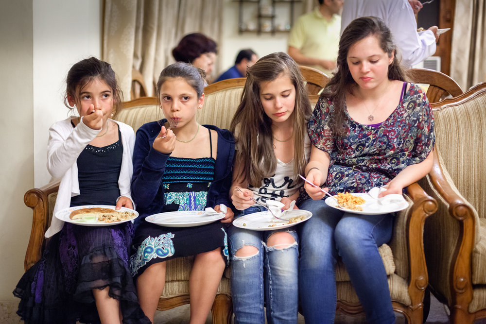 Party Girls : We were visiting family in India. It was our first time there, and my daughters and niece didn't know anyone -- the people were different, the food was different. They squeezed together on the couch during the party and just watched what was going on.