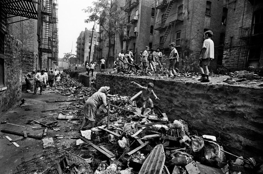 Young children playing while older ones helped with cleanup in the Bronx in July 1966 ©  Jean-Pierre Laffont