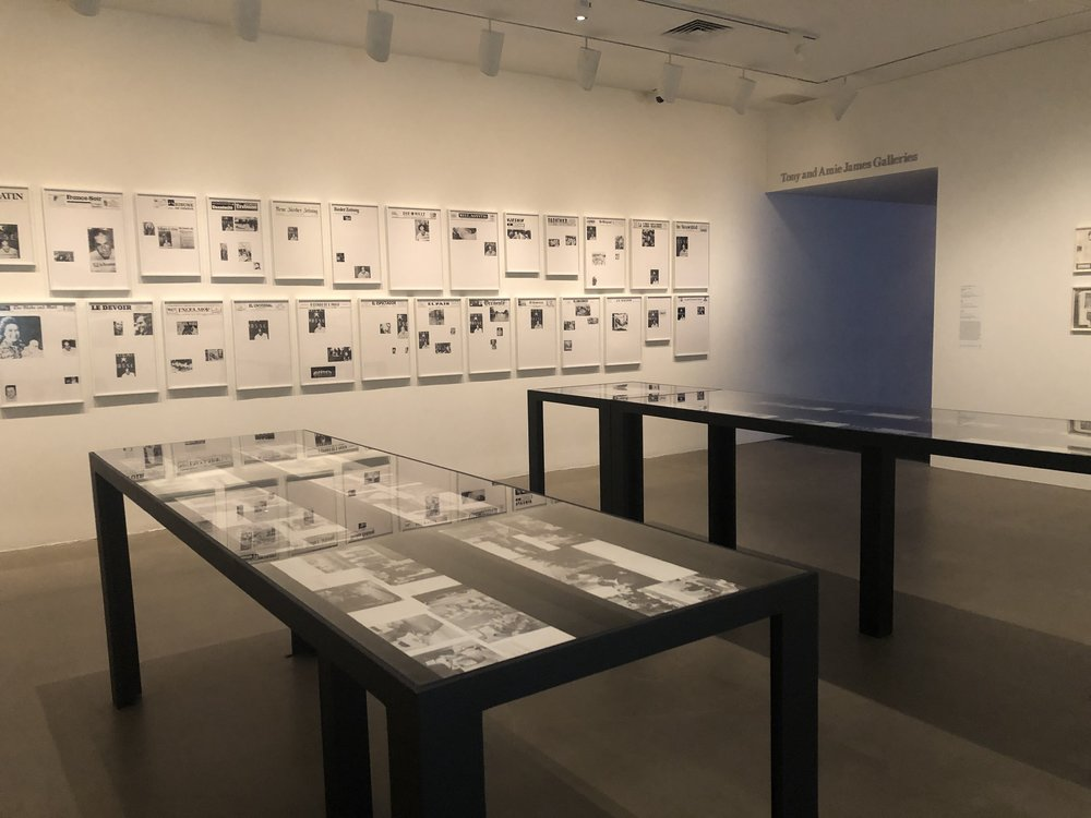 """Alfredo Jaar """"Searching for K"""" (1984), 18 panels, paper works mounted on cardboard (in display) and Sarah Charlesworth """"April 21 1978"""" (1978), chromogenic prints (on wall)."""