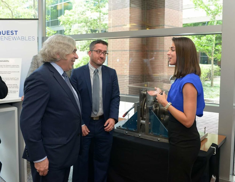 Emrgy ceo Emily Morris and coo Curtis WAtkins showing secretary Moniz the magnetic gearbox