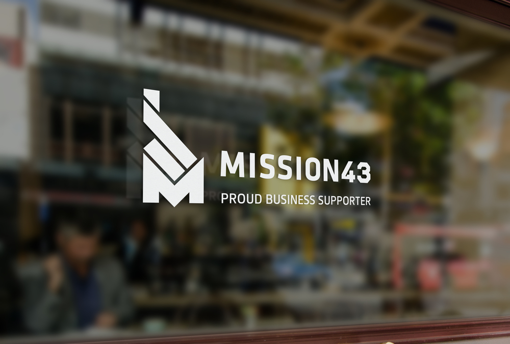An image displaying the Mission43 logo as a sticker on a window