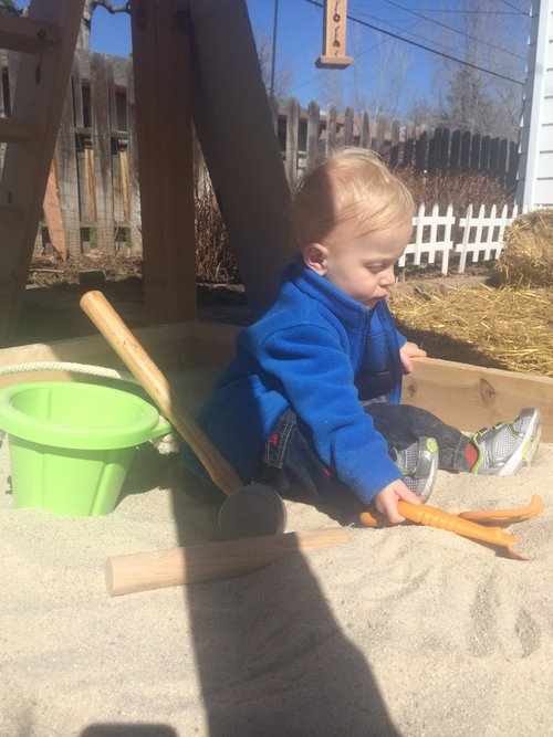 Thomas enjoying the new sandbox under the slide
