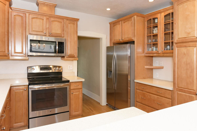 Stainless steel appliances and neutral paint complete the space