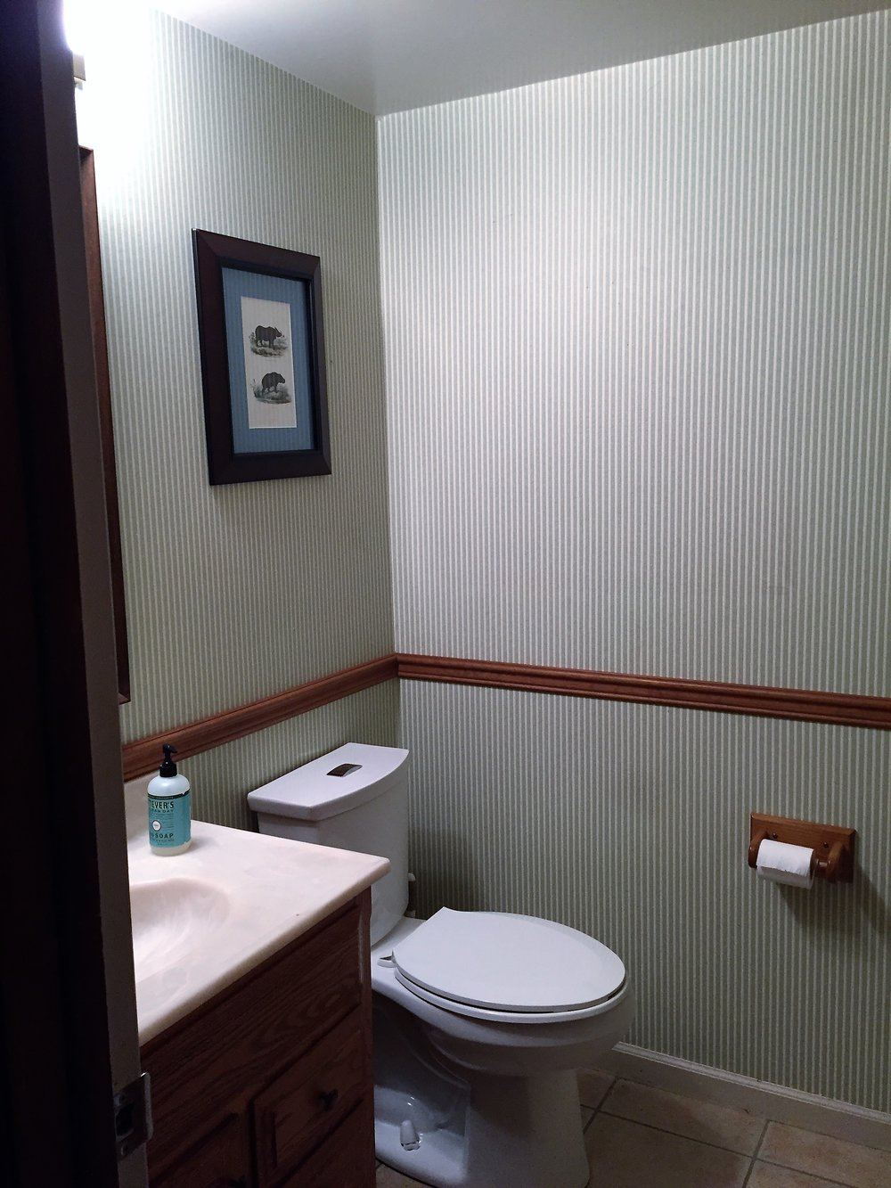 Dated half bathroom with old wallpaper