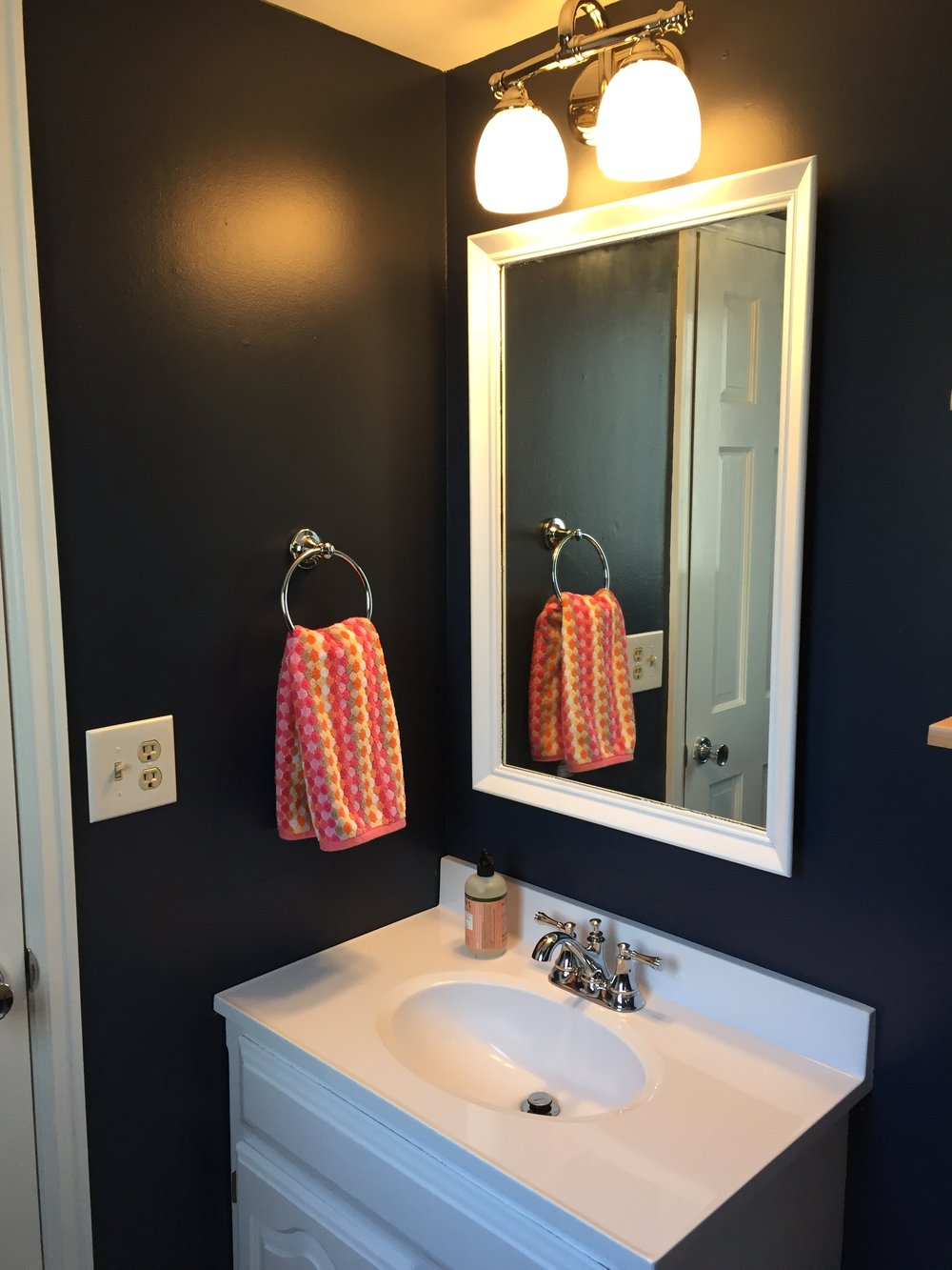Updated bathroom vanity with painted mirror and new light fixture.