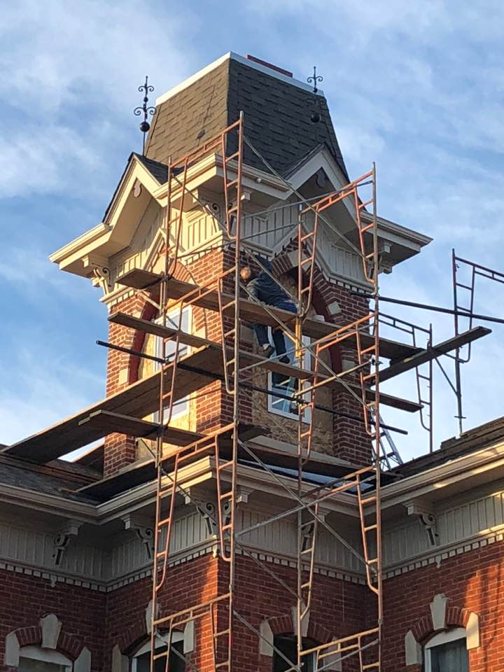 Painting the trim on the tower of the house