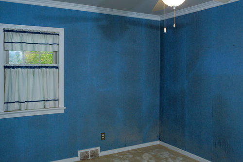 Before. the first floor bedroom was filthy from smoke and the blue wallpaper and dirty carpet had to go.