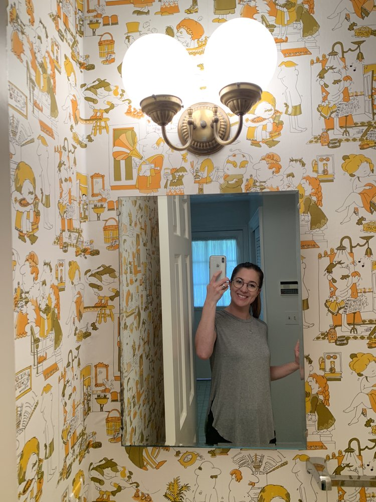 The retro half bathroom with 1970's comic wallpaper and the original sink and toilet.