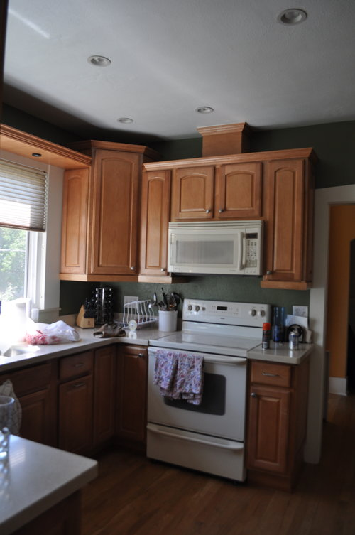 The kitchen before felt very small with the dark green paint and white appliances.