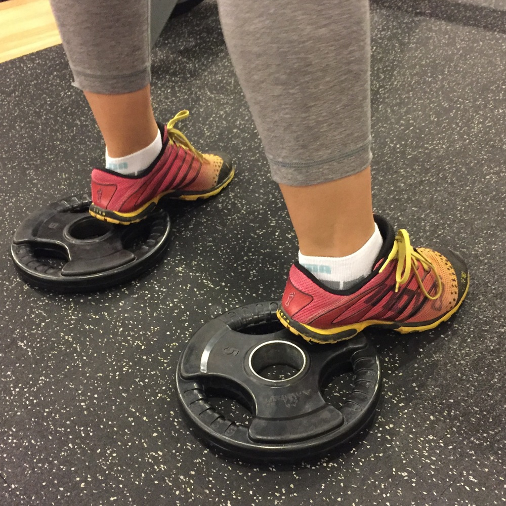 Elevate your heels to improve your squat range of motion or to simply emphasize your quadriceps more.